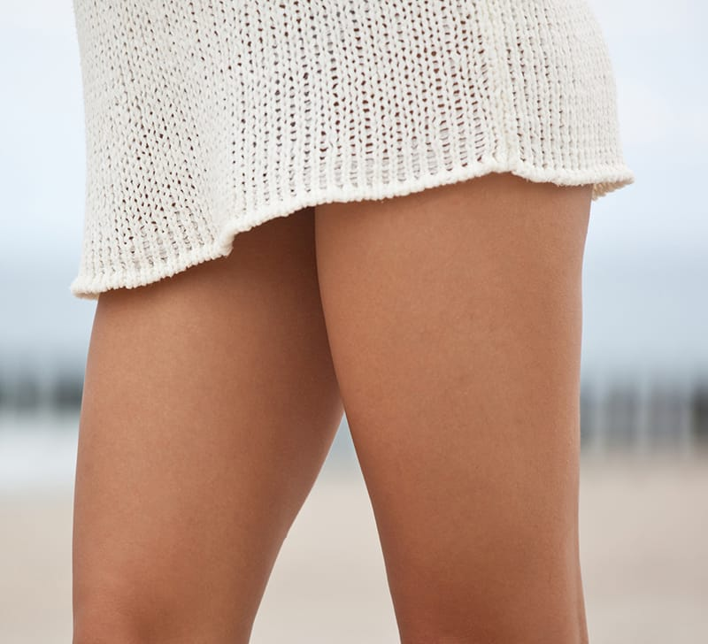 Close up of a woman's thighs in a knit skirt